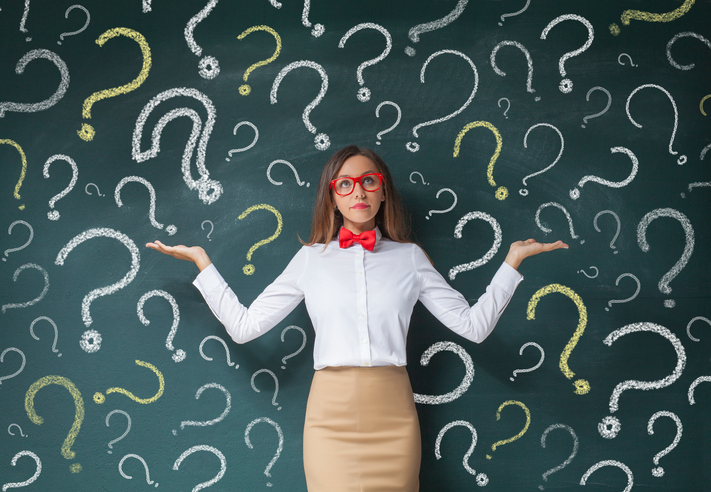 Business woman with question mark on a blackboard