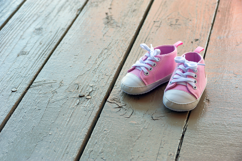 Pink baby girl shoes on a wooden floor outdoors
