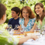 Happy family having lunch together at table in backyard