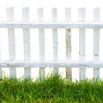 Old wood white fence and green grass.