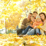 Happy smiling family relaxing in autumn forest