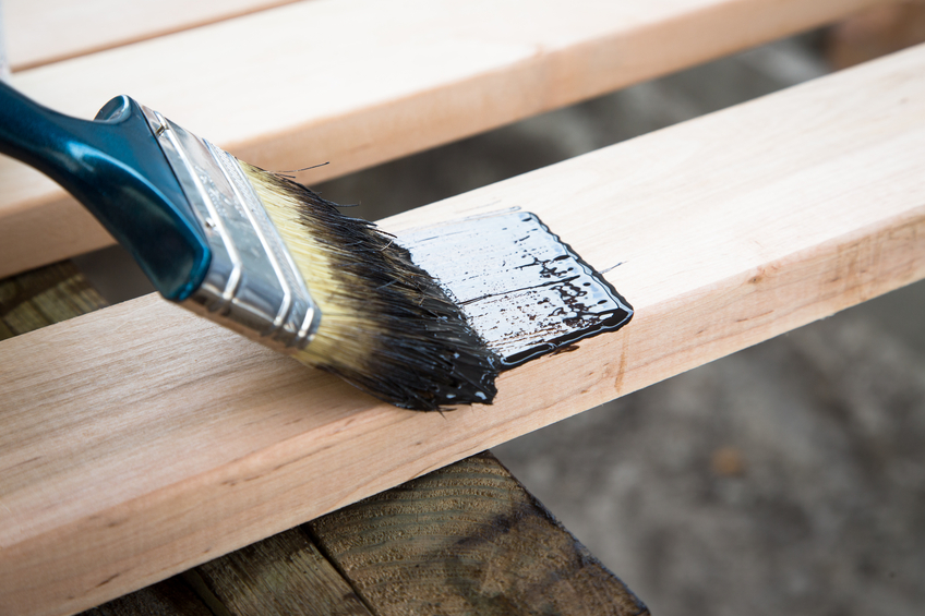 Varnishing natural wood with paint brush. Wood texture and paintbrush - housework background