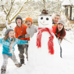 Family Having Fun Building Snowman In Garden