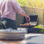 Stack of plates on a table outside in a garden with a man attending to a barbecue in the background