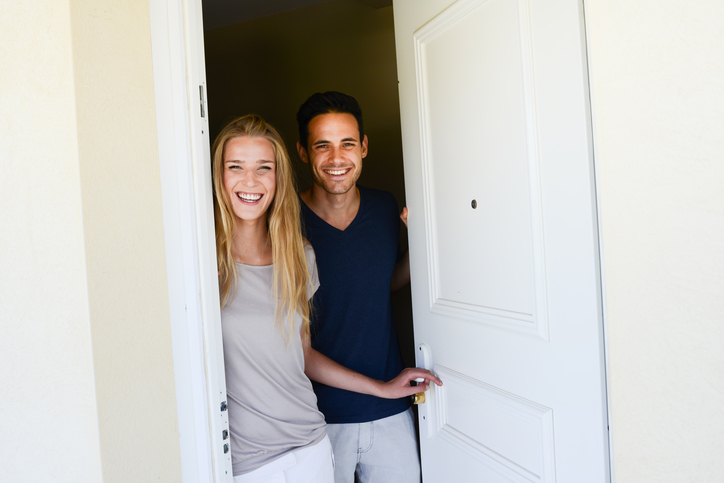 happy young couple man and woman opening door of their new home entrance