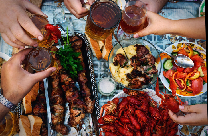 Feast of beer, meat skewer and crayfish. The top view on the group of people who dine outdoors.