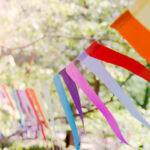 Close up of a colorful party banner tied between trees in a park at an open air celebration event.