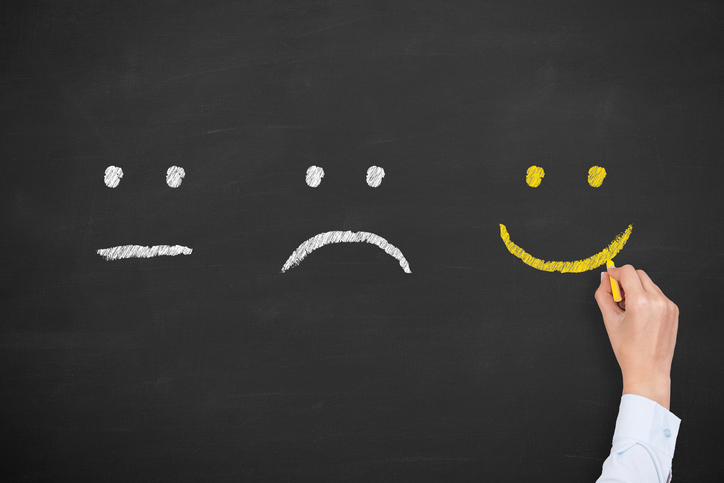 Unhappy and happy smileys on chalkboard